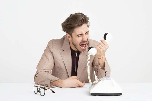 Man Wearing Brown Suit Jacket Mocking On White Telephone 1587014